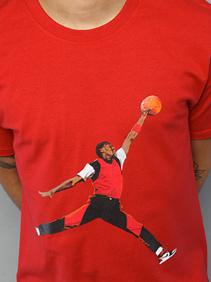 Picture of red T-shirt with graphic print of a jumping basketball player